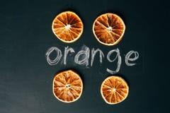 Arancia affettata quattro tazze su un bordo nero del fondo Immagini Stock