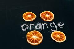 Arancia affettata quattro tazze su un bordo nero del fondo Fotografie Stock Libere da Diritti