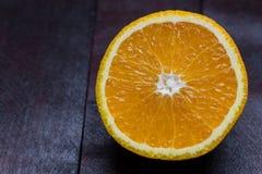 Arancia affettata su fondo di legno di mogano fotografia stock libera da diritti