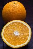 Arancia affettata su fondo di legno di mogano immagine stock