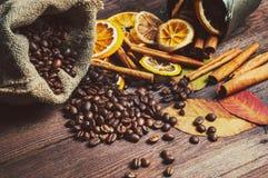 Arancia e limone asciutto, chicchi di caffè nella borsa, cannella e foglie di autunno cadute immagine stock