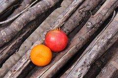 Arancia e melograno disposti su legno Fotografia Stock