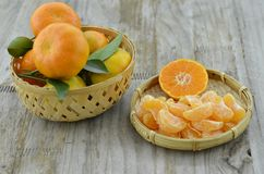 Arancia fresca sbucciata in canestro di vimini su fondo di legno immagini stock libere da diritti