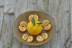 Arancia fresca sbucciata in piatto su fondo di legno immagini stock libere da diritti