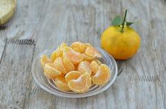 Arancia fresca sbucciata in piatto su fondo di legno fotografie stock libere da diritti
