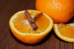 Arancia succosa mezza con i bastoni di cannella su un bordo di legno fotografia stock libera da diritti