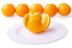 Arancia sul piatto con fondo vago Immagine Stock