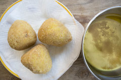 Arancine fried in boiling oil. Street food : fried sicilian rice balls or arancini Royalty Free Stock Photo