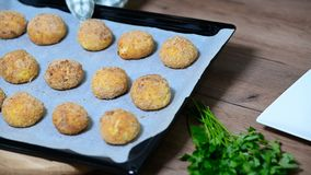 Arancini baked with cheese cutlets dish covered with bread crumbs, panko crumbs on a cutting board next to baking tray. Arancini baked with cheese cutlets dish stock video footage
