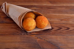 Arancini balls. Fried rice balls in paper on brown wooden background. Snack. Rice recipe. Rice cakes. Rice balls. Fried rice balls Stock Photos