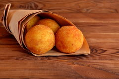 Arancini balls. Fried rice balls in paper on brown wooden background. Snack, sicilian street food Royalty Free Stock Photos