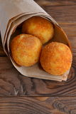 Arancini balls. Fried rice balls in paper on vintage wooden table. Snack. Close-up. Rice recipe. Fried rice balls Stock Images