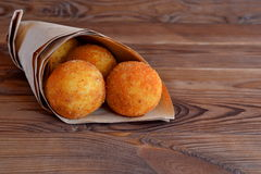 Arancini balls. Fried rice balls in paper on brown wooden background. Snack Royalty Free Stock Photography