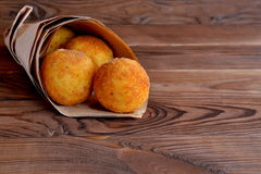 Arancini balls in paper on brown wooden background Stock Images