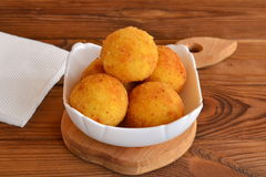 Arancini balls on a plate. Fried rice cutlets recipe. Brown wooden table Royalty Free Stock Photography
