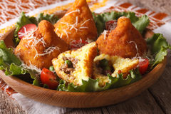 Arancini with meat and peas close-up on a plate. Horizontal. Arancini rice balls with meat and peas close-up on a plate. Horizontal Stock Image