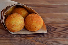 Arancini rice balls. Fried rice balls in paper on brown wooden background. Snack, street food Royalty Free Stock Photo