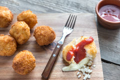 Arancini - rice balls with mozzarella. On the wooden board Stock Photos