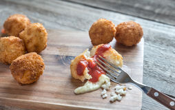Arancini - rice balls with mozzarella. On the wooden board Stock Image