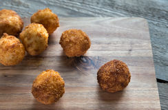 Arancini - rice balls with mozzarella. On the wooden board Stock Photography