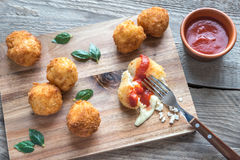 Arancini - rice balls with mozzarella. On the wooden board Stock Images