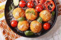 Arancini rice balls with parmesan closeup. horizontal top view. Fried arancini rice balls with parmesan and fresh vegetables on a plate. horizontal view from Royalty Free Stock Photo