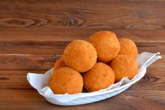 Arancini rice balls on a plate. Fried rice balls recipe. Brown wooden background. Rice patties. Fried rice balls. Arancini recipe. Arancini dish Royalty Free Stock Photos