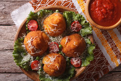 Arancini rice balls and tomato sauce closeup. horizontal top vie. Arancini rice balls stuffed with meat and tomato sauce closeup on a table. Horizontal top view Royalty Free Stock Image