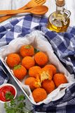 Arancini - saffron rice balls stuffed with cheese. In baking dish on old wooden table with kitchen towel, tomato sauce, olive oil and shovels on background Stock Photo
