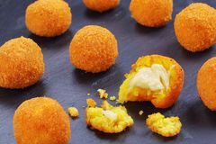 Arancini - saffron rice balls stuffed with cheese. Delicious hot italian arancini - saffron rice balls stuffed with melted cheese on black slate tray,  view from Royalty Free Stock Photo