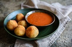 Arancini - traditional deep fried rice balls with meat and cheese. Arancini - traditional Italian deep fried rice balls with meat and cheese, served with tomato Royalty Free Stock Images