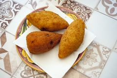 Arancini - traditional fired rice. Three arancini, a typical rotisserie product, consisting of rice stuffed with minced fried meat, arranged on a plate royalty free stock photos