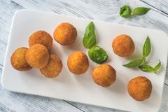 Arancini on the white plate. On the wooden table Royalty Free Stock Image
