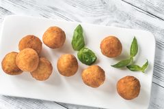 Arancini on the white plate. On the wooden table Stock Image