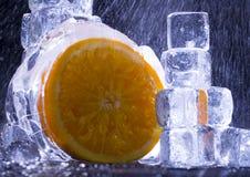 Arancio con i cubi di ghiaccio Fotografie Stock Libere da Diritti