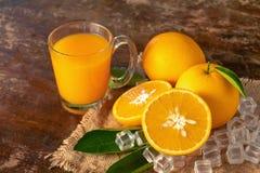 Arancio fresco e un vetro di succo d'arancia su un backg di legno della tavola Fotografia Stock Libera da Diritti