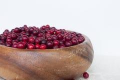 Arandos das bagas em um prato feito a mão de madeira Fotografia de Stock Royalty Free