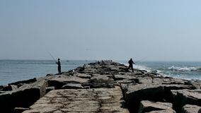 Aransas portuario, TX - 27 DE FEBRERO DE 2017: Pesca del pescador en un embarcadero de piedra largo almacen de video