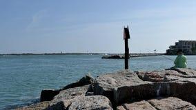 Aransas portuario, TX - 6 de marzo de 2016: Pescador en rocas en la entrada del puerto deportivo almacen de metraje de vídeo