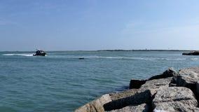 Aransas portuario, TX - 6 de marzo de 2016: Pescador en rocas en la entrada del puerto deportivo metrajes