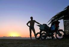 Arapov Sergey με μια μοτοσικλέτα σε ένα υπόβαθρο ηλιοβασιλέματος. Στοκ Εικόνες