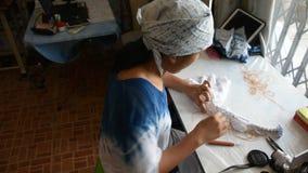arashi泰国的妇女工作处理折叠捆绑和缝合或者在织品的shibori 股票录像