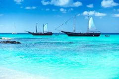 Arashi Beach Aruba West Indies boats catamaran snorkeling turquoise water. Arashi Beach, Aruba, West Indies: 2 tour boats anchored for tourists to go swimming or Royalty Free Stock Photography