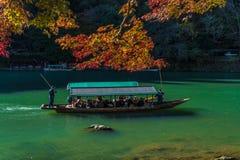 Arashiyama, Japan- Nov 29, 2015 : Group of Tourists cruising wit. H blue jacket Japanese Ferryman in the River at Arashiyama on 29 Nov Stock Photos