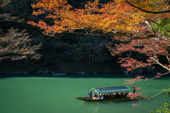Arashiyama, Japan- Nov 29, 2015 : Group of Tourists cruising wit. H blue jacket Japanese Ferryman in the River at Arashiyama on 29 Nov Stock Photo