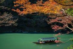 Arashiyama, Japan- Nov 29, 2015 : Group of Tourists cruising wit. H blue jacket Japanese Ferryman in the River at Arashiyama on 29 Nov Stock Photo