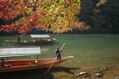 Arashiyama. Kyoto,Japan, 6 November 2015 A sightseeing boat with passengers rowing in Katsura River with red maple tree, Kyoto, Japan Stock Images