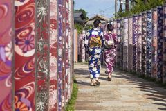Arashiyama, Kyoto, Japan - September 18 2017: Two woman with kimonos walk through poles with traditional kimono cloth. Arashiyama, Kyoto, Japan - September 18 Stock Images