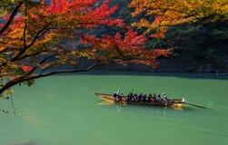 Tourists enjoy boat cruise tour and beautiful surrounding autumn foliage. Arashiyama, Kyoto : On November 17,2013 - Tourists enjoy boat cruise tour and Stock Image