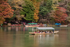 Arashiyama travel. Kyoto, Japan - November 26,2015 :  Unidentified people sail boates in the Oi river for tourist who travel to Arashiyama mountain area in Kyoto Stock Image